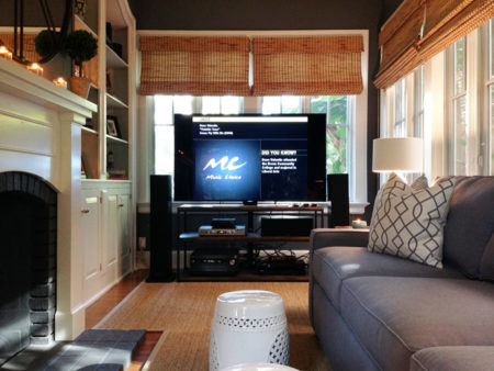a large TV with complete entertainment equipment in front of the window