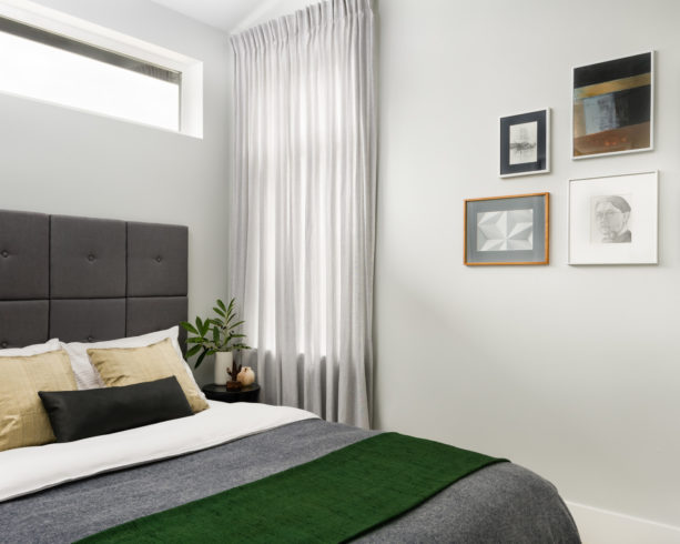 a basil green throw blanket placed on a grey bed