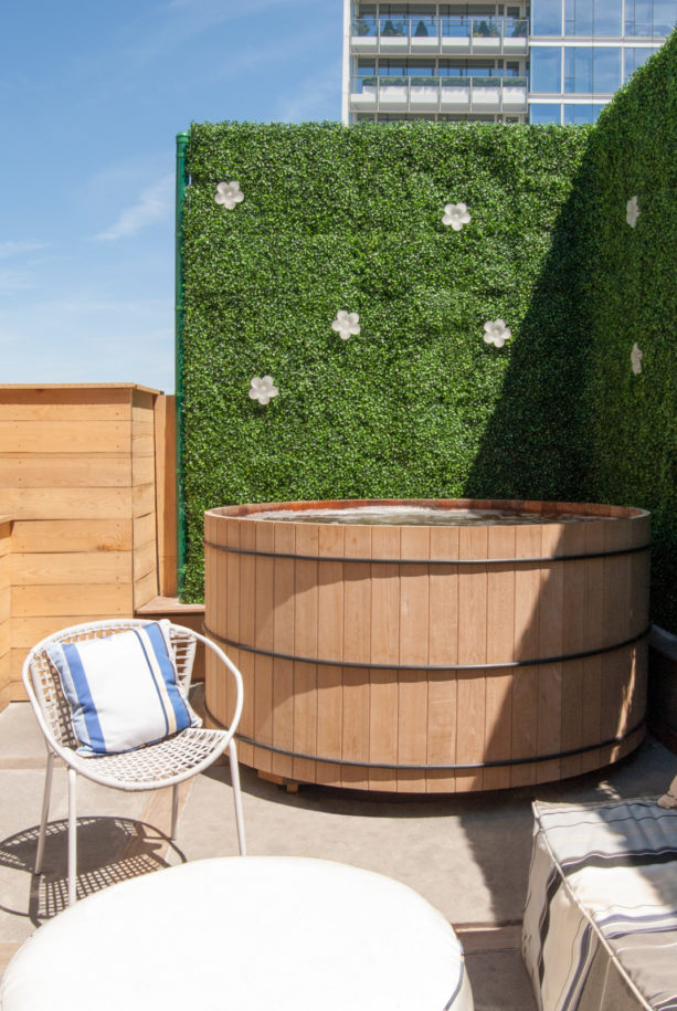 a beautiful screen created from faux hedge plant panels to add privacy to a hot tub