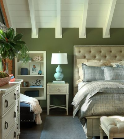 a bed with gray bedding set in a bedroom dominated with green