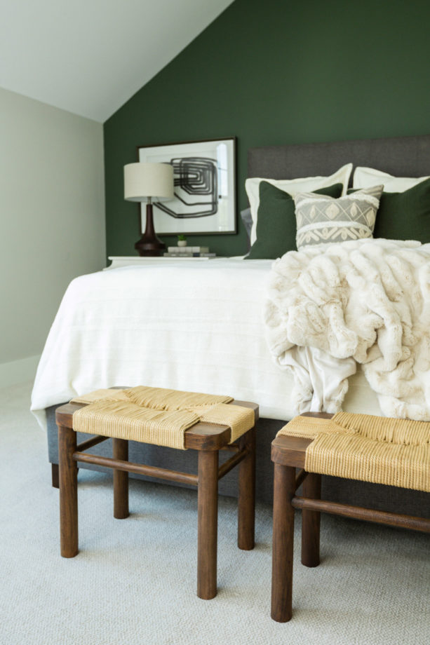 a traditional guest room with ash gray bed and pine green accent wall