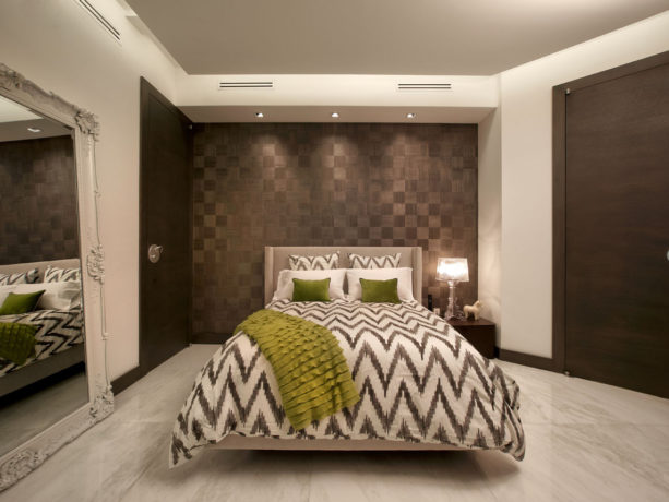 a white and gray bed adorned with decorative pear green throw