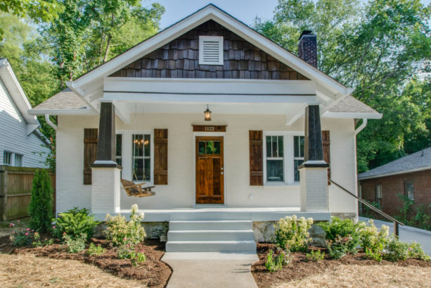 a craftsman house with painted white brick and stained wood combination