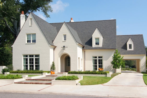 an off-white painted-brick home with grey roof shingles