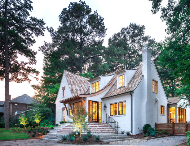 white-painted brick home with unique single gable roof and red brick accents