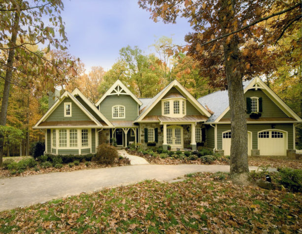 a creamy green vinyl siding exterior in a sizeable ranch style two-story home