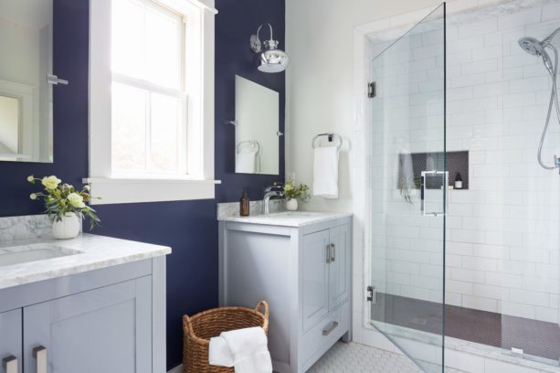 a farmhouse bathroom with clean white floor and navy blue walls for contrast