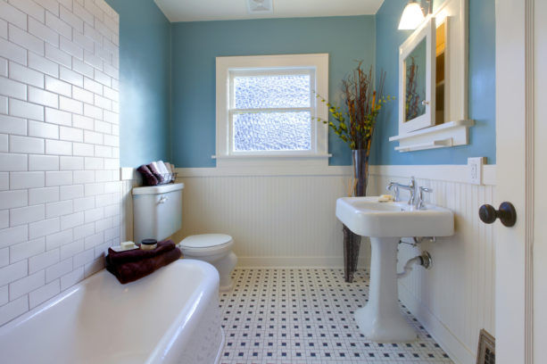 a traditional bathroom with monochrome style combined with blue wall and white-colored tub