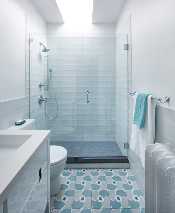 a transitional bathroom with pale blue ceramic tiles and white wall