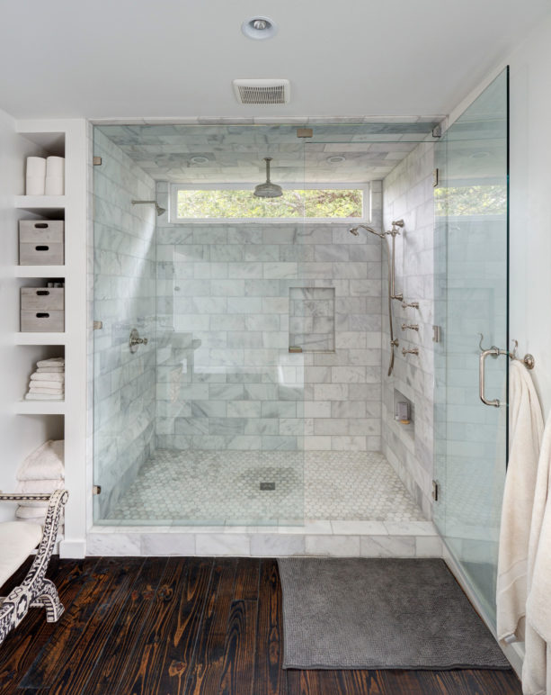 alcove shower in a contemporary white-tiled master bathroom without a tub
