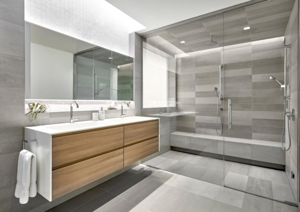 grey master bathroom without a tub completed with light-wood cabinets