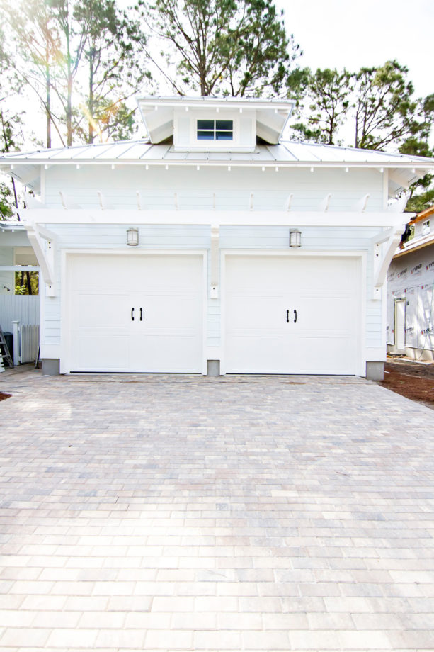huge beach style detached two-car carport in front of a crisply white garage