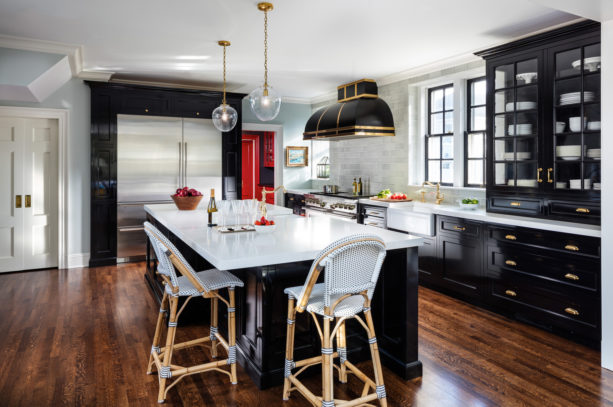 large country kitchen equipped with polished white cabinets and glossy black countertops