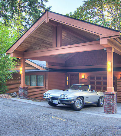 sizeable arts and crafts carport in front of a wooden siding garage