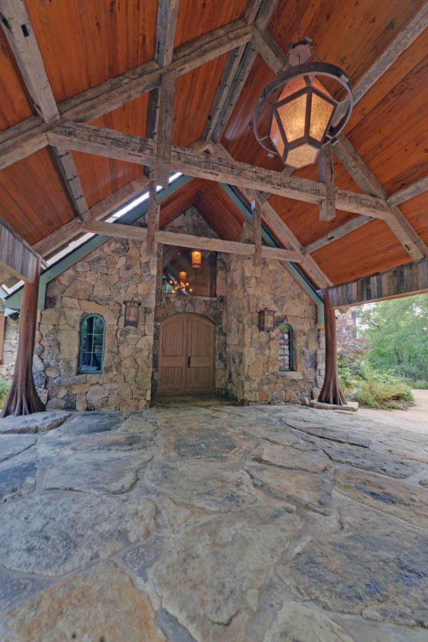 a post and beam carport with a stamped concrete driveway in a lake house