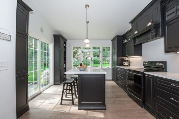 black floor to ceiling cabinets with solid surface countertops