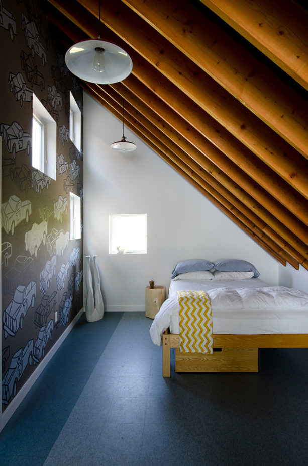 loft-style attic bedroom with mural paintings and wood slanted walls