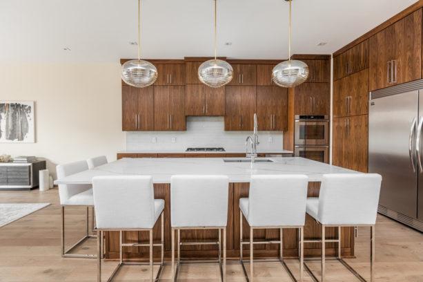 medium tone wood flat panel floor to ceiling cabinets with white backsplash