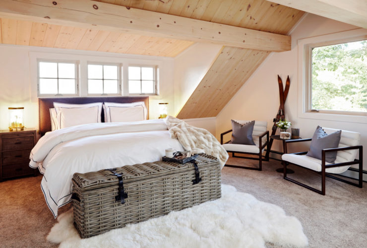rustic attic bedroom with vaulted ceiling and slanted walls in a natural wood finish