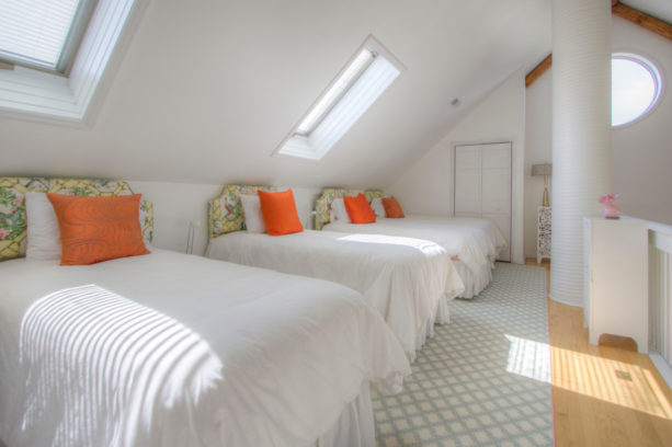 spacious guest's bedroom in the attic with polished slanted walls