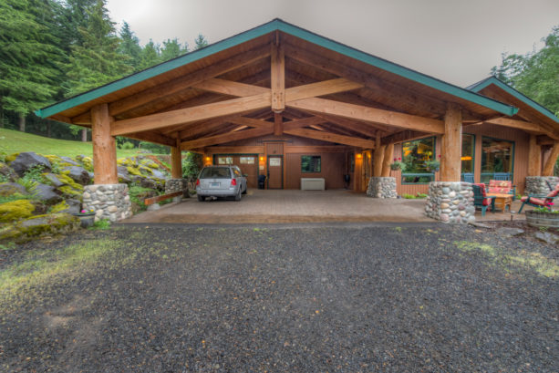 spacious mountain style post and beam carport with green trim