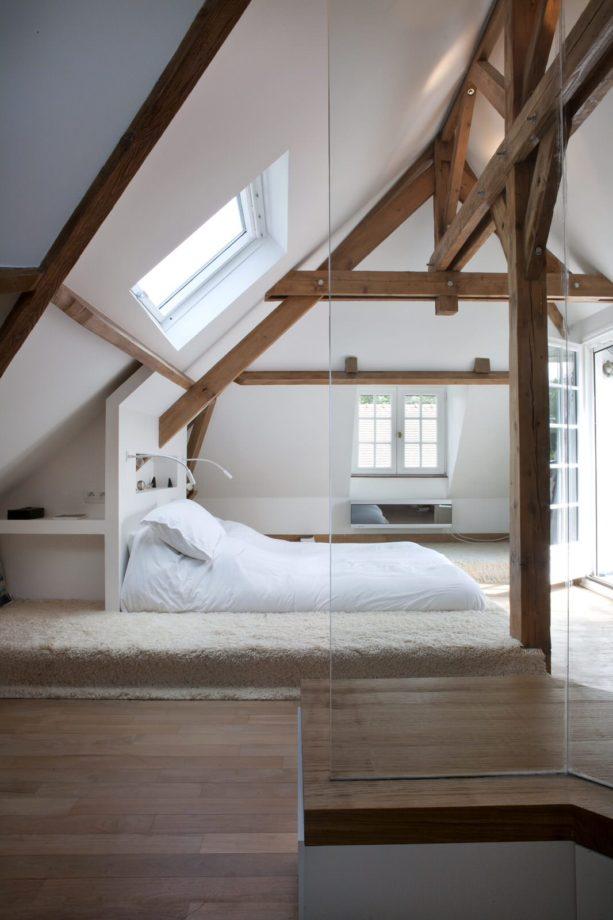unique mid-sized attic bedroom with medium tone accent slanted walls