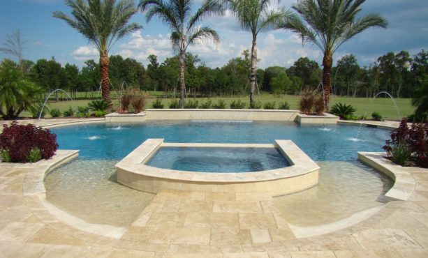 a grecian shaped pool with travertine stamped concrete decking around