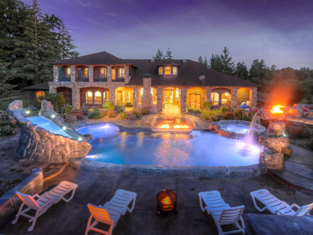 a huge mediterranean styled kidney pool with stamped concrete around