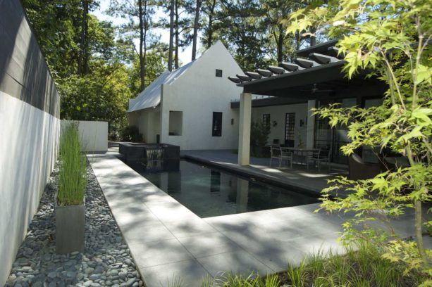 a minimalist backyard with stamped concrete around a rectangular pool