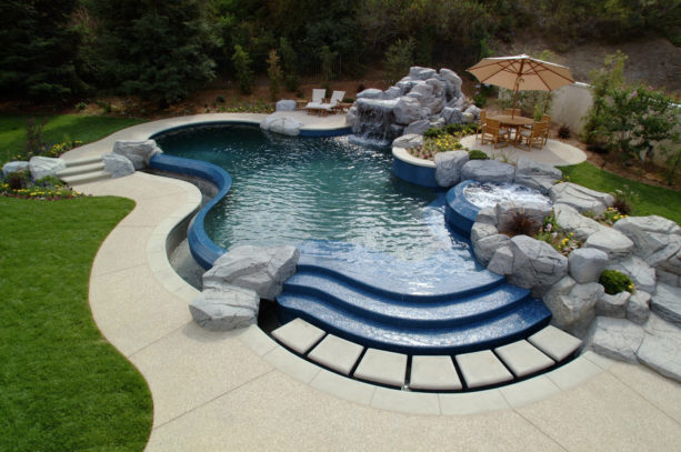 a sizeable pool with fountain and stamped concrete and artificial rocks