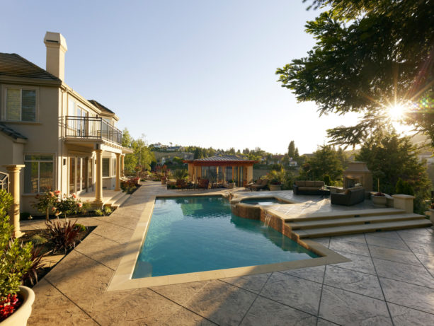an extensive stamped concrete pool deck with a raised hot tub