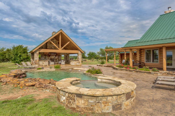 mountain style backyard area with stamped and stained concrete around a pool