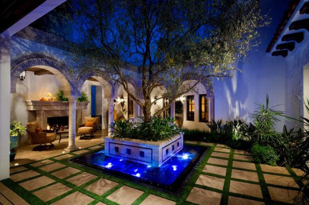 spanish mediterranean style home featuring a courtyard with stunning water feature