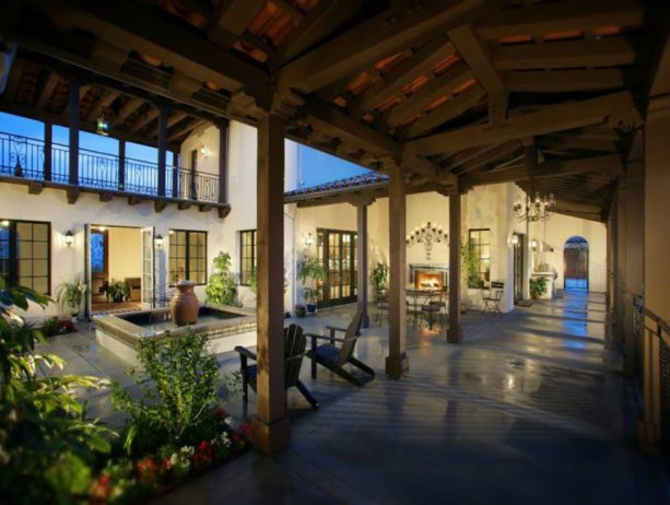 spanish style split-level home featuring a courtyard with a fountain