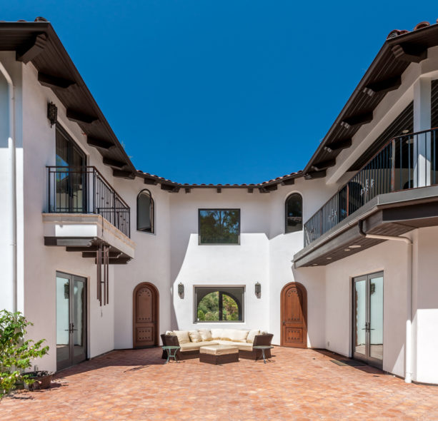 u-shaped courtyard surrounded by spanish style balconies in a white exterior home
