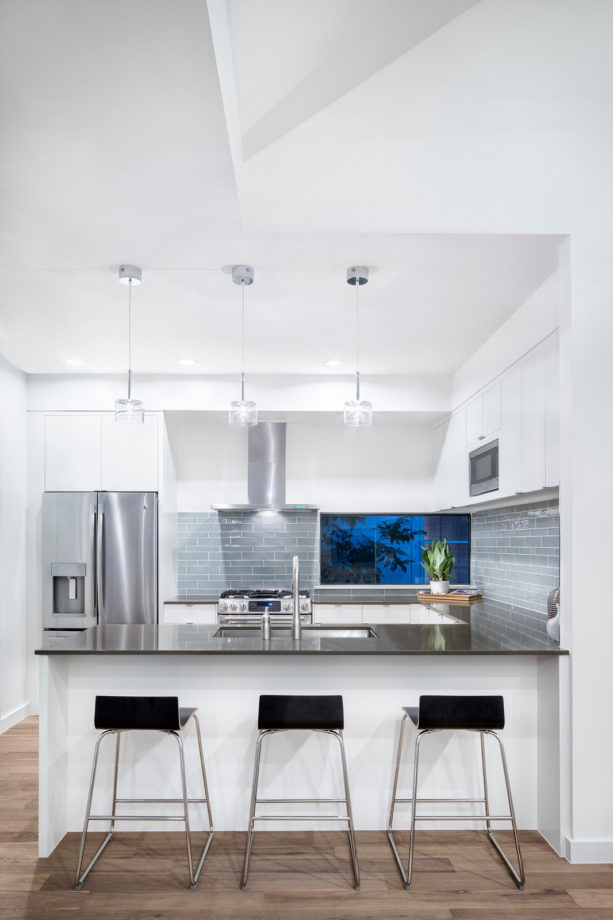 black solid surface countertops kitchen peninsula with low back stools seating
