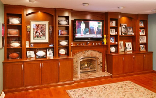 classic living room with wood wall unit decorative shelving and marble fireplace