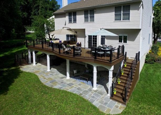 flagstone patio under a dark wood deck idea