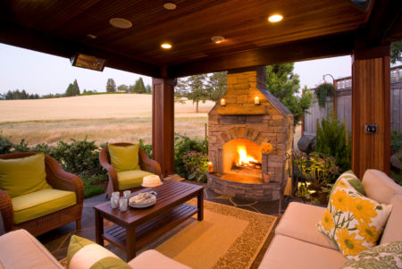 slate carpeted covered patio with fieldstone fireplace