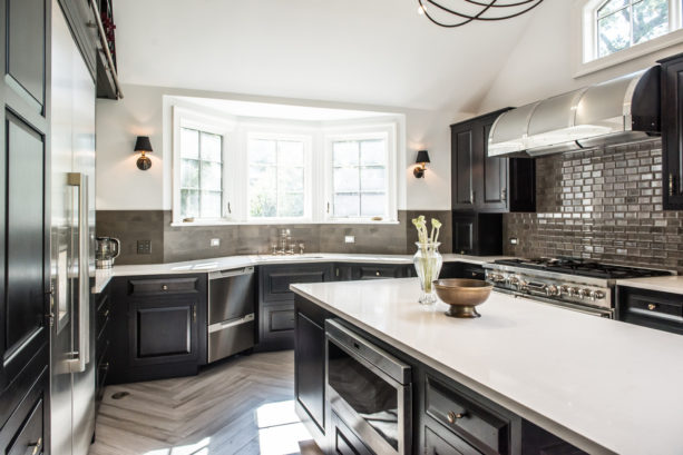 u-shaped kitchen with bay windows over a single bowl sink
