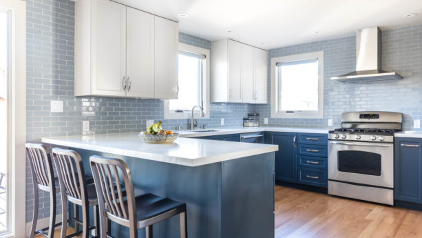 u-shaped kitchen with blue shaker cabinets and a peninsula