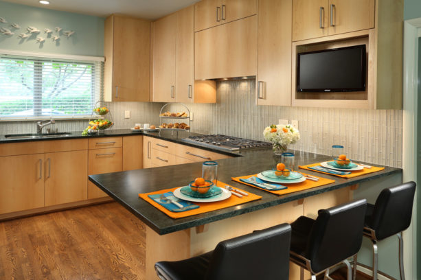 u-shaped trendy kitchen with medium tone wood floor and a peninsula with black soapstone countertops