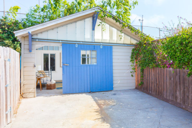 bold blue side sliding garage door combined with gray siding
