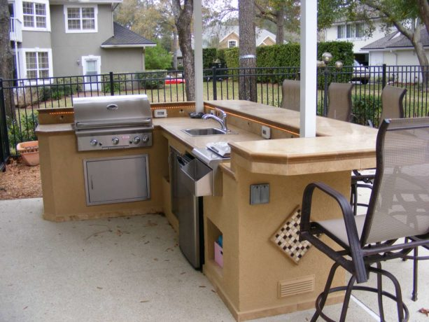 classic l-shaped outdoor stucco finished kitchen completed with bar seating area