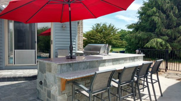 conventional l-shaped outdoor kitchen with an umbrella on the countertops