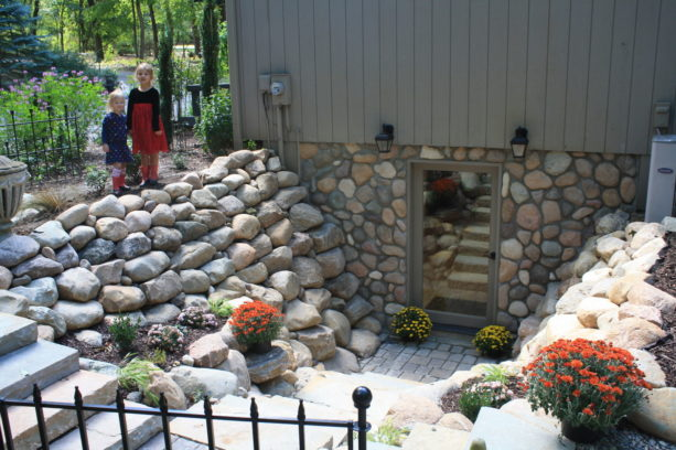 hinged glass door option with a gray frame in a stone walled walkout basement