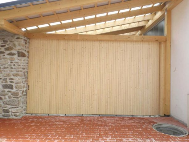 the combination of natural stacked stone wall, brick paver, and a contemporary side sliding garage door