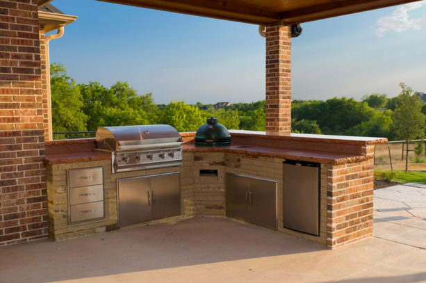 transitional covered l-shaped outdoor kitchen with exposed red brick walls