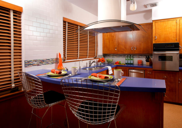 unique combination of brown flat-panel cabinets and cobalt blue countertop kitchen color to give a bold look