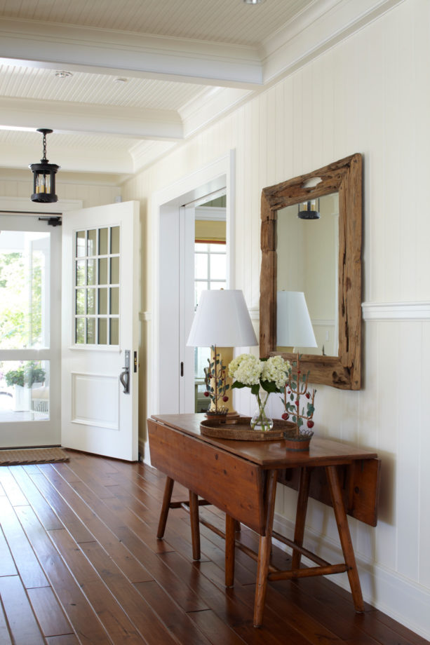 crisp white small entryway with walnut flooring